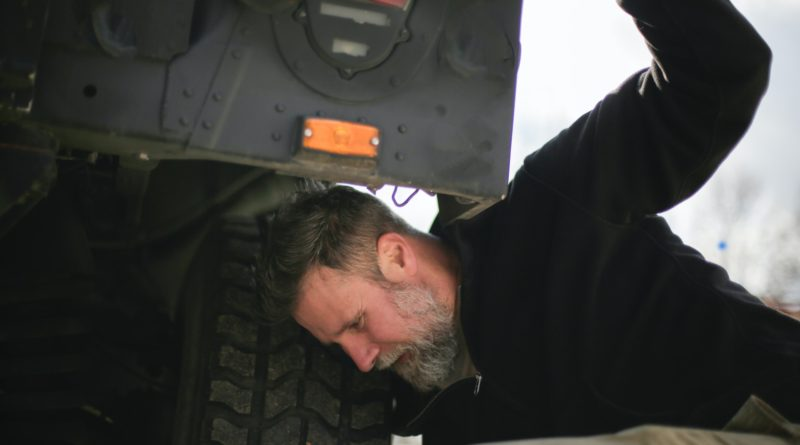Person checking their tyres for signs