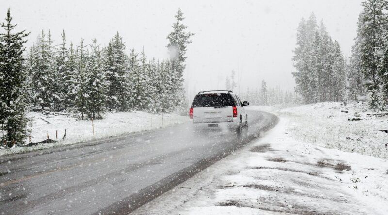 Car driving down a snowy road in the winter